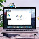 Frosch sitzt auf Notebook und hält Smartphone mit Google Ads Logo
